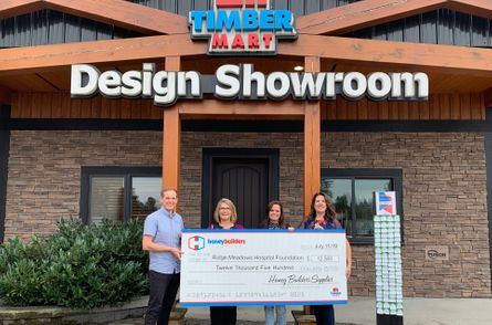 Design showroom team holding a cheque